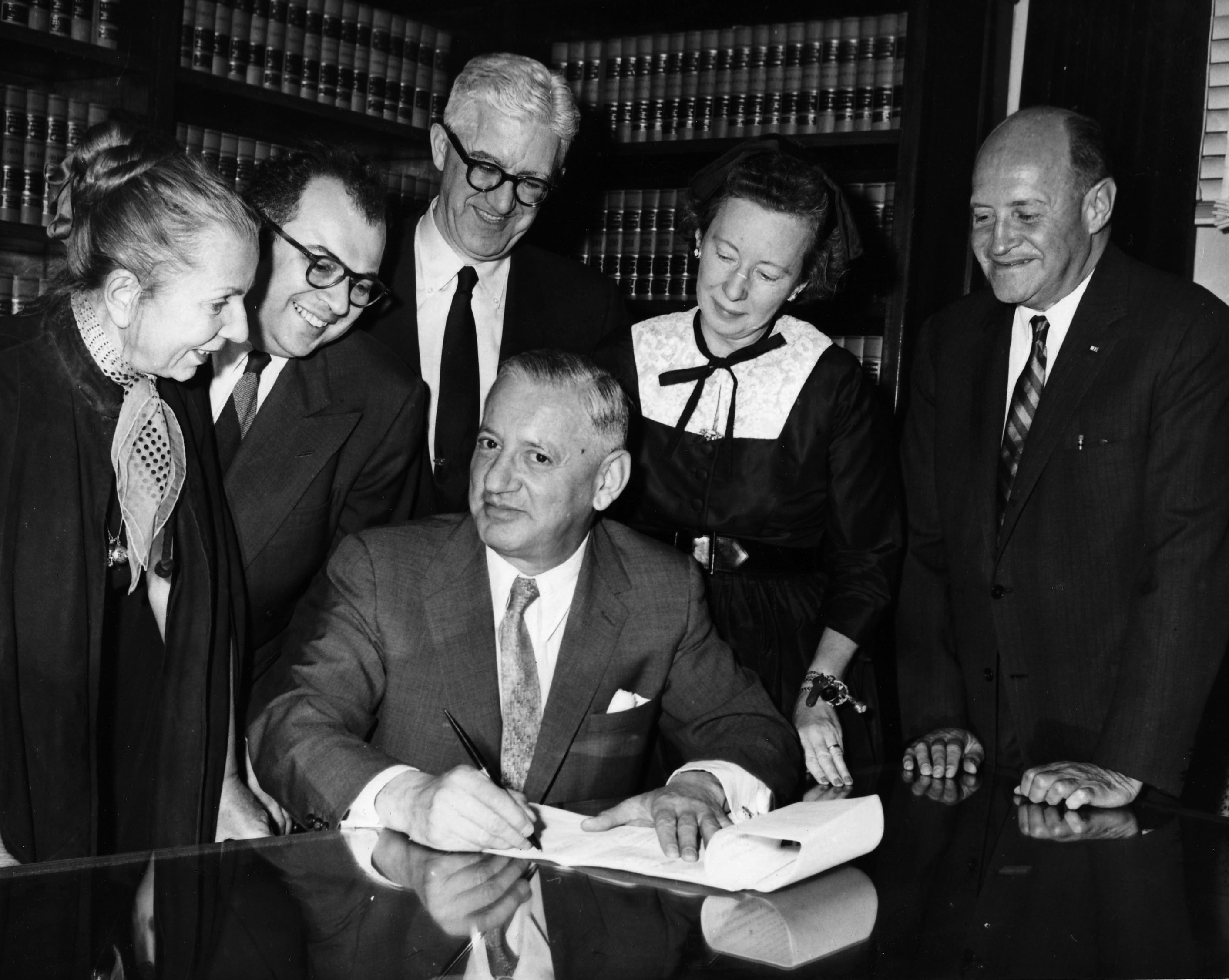 Judge Saul Streit, Presiding Justice of the New York Supreme Court (seated), signs the incorporation documents witnessed by original Members (left to right) Hanya Holm, Ezra Stone, Shepard Traube, Agnes de Mille + legal counsel Erwin Feldman.
